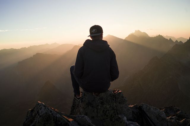 man-sittting-and-watching-sunrise-on-mountain-top