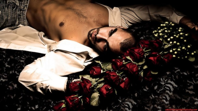 man on a bed of red roses